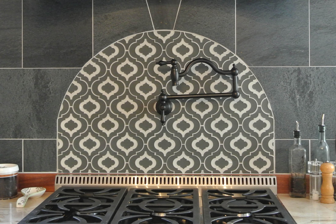 Arabesque shaped, back painted glass mosaic tile in gray and white. Custom kitchen feature.