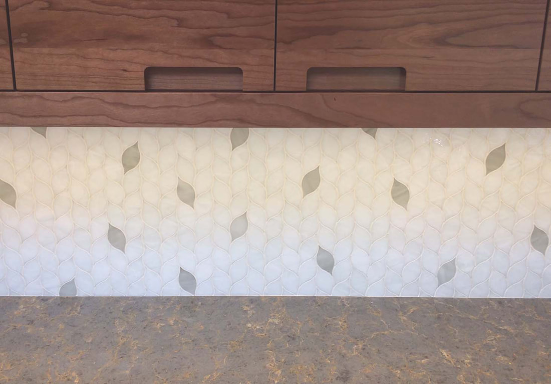 Leaf shaped art glass mosaic tile in white and grey tones. Kitchen backsplash.