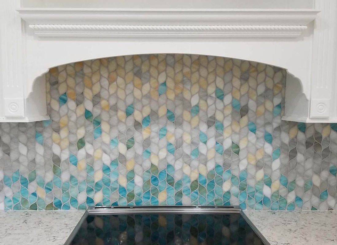 Leaf shaped gradient art glass mosaic in blue, green and yellow tones. Kitchen backsplash.